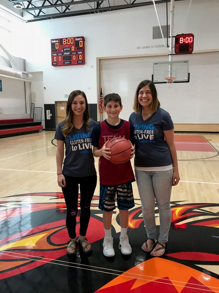 Jackson Resin stands with a basketball alongside Laura Boone and Jena Fellenzer.